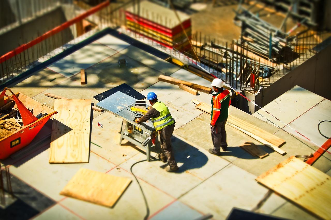 Zwei Männer arbeiten auf einer Baustelle. Dafür ist eine Einweisung an der Maschine nötig.